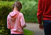 En flicka med flätor går tillsammans med en vuxen på en grusväg.