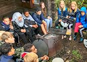 Elever sitter i en ring vid ett vindskydd