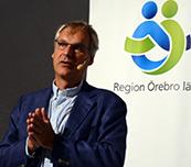 John Holmberg föreläser, en bild på Region Örebro läns logotyp i bakgrunden.