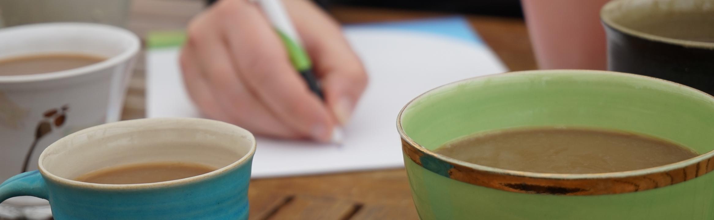 Kaffekoppar och hand som skriver - Kulturplan 2020-2023