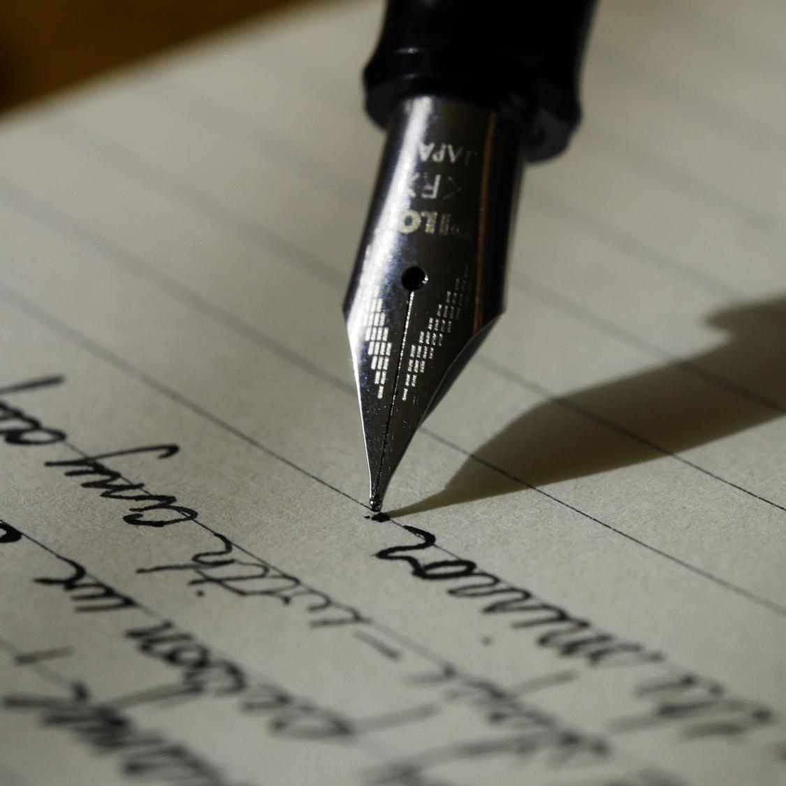 Bläckpenna skriver på linjerat papper